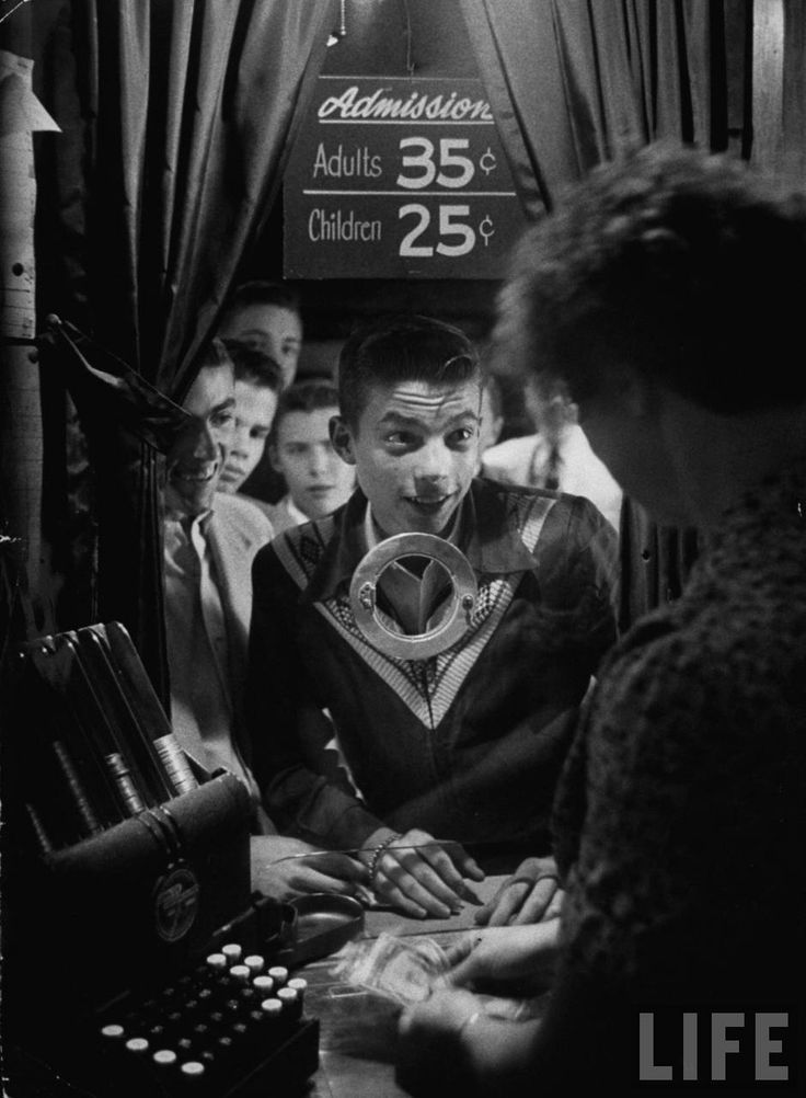 Teenage boy peering into window of ticket booth at a movie theater. West Hartford, Connecticut, 1954.  By Yale Joel