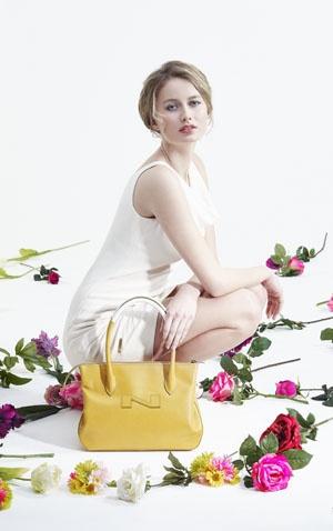 Model met gele Nathan handtas op een bloementapijt