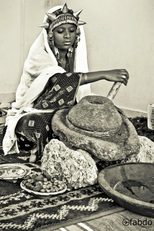 Image of a gorgeous berber woman making argan oil the traditional way. Check out the silver headgear!)