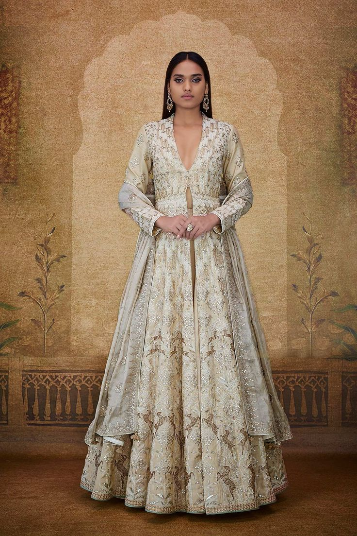 A gold tissue A-line jacket with long sleeves, plunging neckline, exquisitely embroidered with gota patti, dori, resham, zardosi and sequin work, paired with a flared A-line gold tissue lehenga, styled with a gold tissue dupatta in gota patti, dori, sequin, zari and pearl work in floral, vine and deer motifs inspired by a whimsical land where the lush forest and glistening desert merge into one to find a universal elixir.