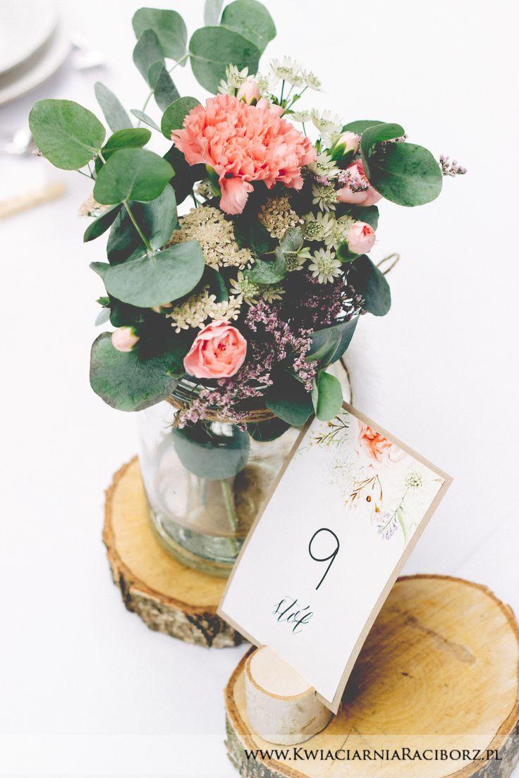 Wystrój stołów na salę weselną - eukaliptus, kwiaty, wszystko w eleganckim słoiczku na drewnianych pieńkach
