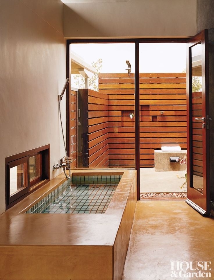 In a South African bath, the tub is clad in pigmented cement and glass doors lead to an outdoor shower.