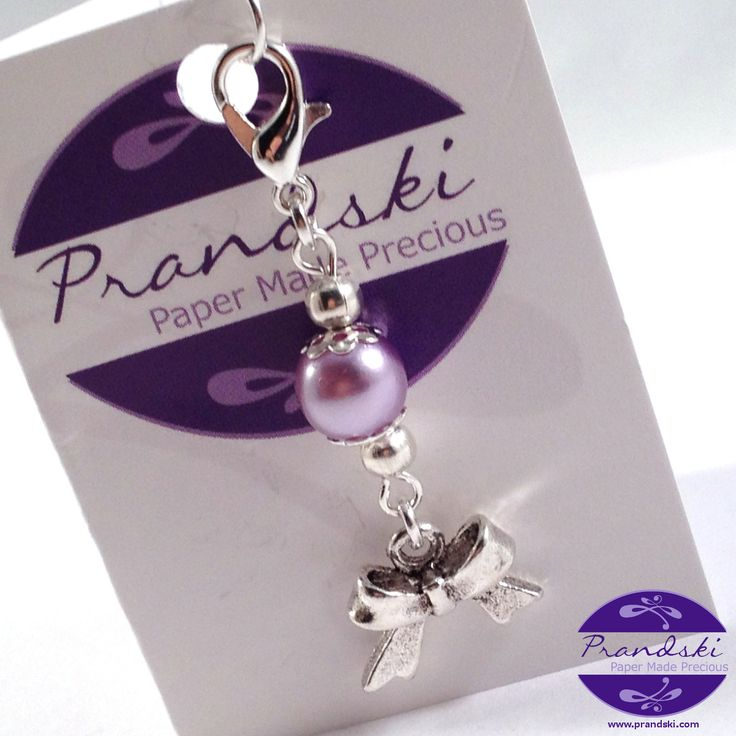 Tibetan silver clip-on charm for link chaincharm bracelets. Lilac faux-pearl and silverribbon tied in a bowcharm with silver plated clip on clasp.Can also be clipped to key rings, handbags, pur...