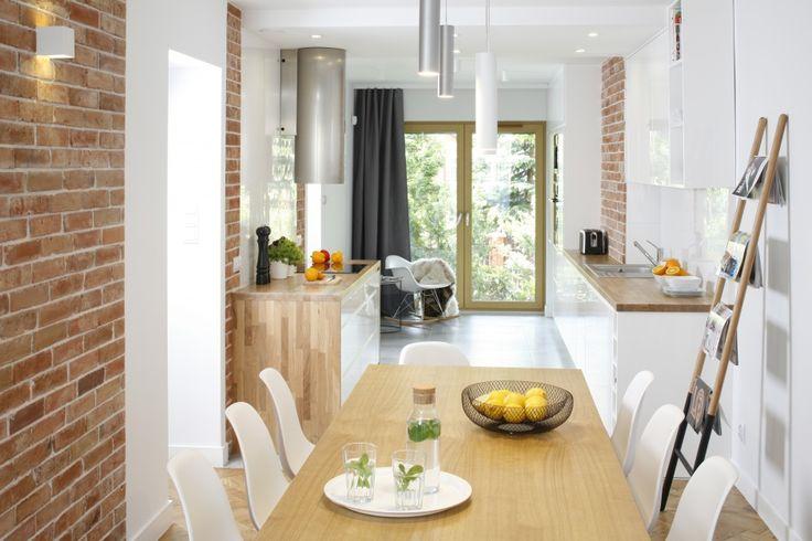 Jadalnia połączona jest z kuchnią. Masywny, drewniany stół doskonale koresponduje z białymi, lekkimi w formie krzesłami. Projekt Agata Piltz. Fot. Bartosz Jarosz.