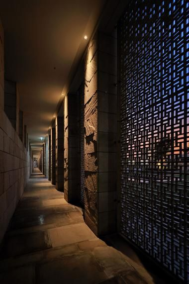 (AMAN NEW DELHI, Taken by TOSHIO KANEKO): Downlights arranged against each of the walls highlight the texture of the walls while creating enough ambient light for people to walk through the halls. The screens between pillars allow daylight to pass through.  I love how the downlights on the pillars make them appear strong and bold, while the screens appear flimsy and delicate because you can see the sunset behind it.