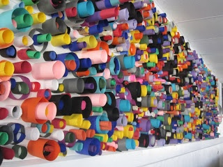 wall art. students make cylinders of different heights, dip in plate of glue + stick to banner paper. great for using paper scraps!
