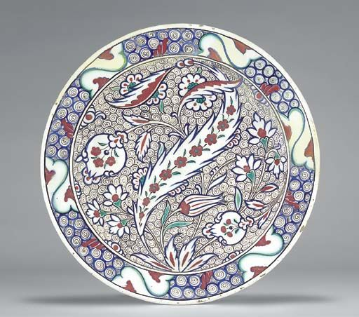 AN IZNIK POTTERY DISH  OTTOMAN TURKEY, CIRCA 1575  With sloping rim on short foot, the white interior painted in blue, green and red with an asymmetric design of large central saz leaf with spine of small red flowerheads, striped tulip, two stylized pomegranates, flowers and smaller saz leaves against ground of densely drawn black scrolls on white, the rim with stylized wave and scroll motif in blue, black, green and red, the exterior completely plain,   12¼in. (31cm.) diam.