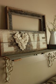 Reclaimed wood, paint, fabric flowers and hot glue.. A great idea for above the bed