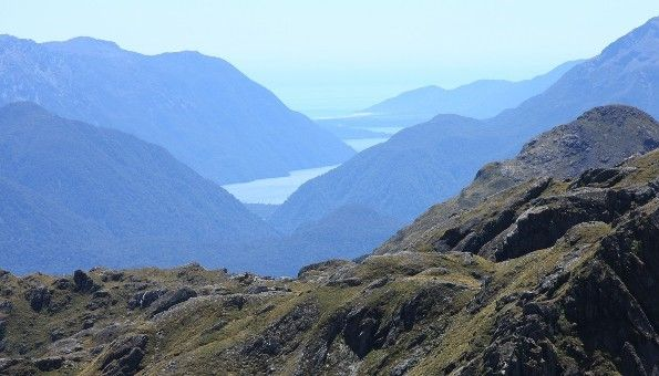 The Routeburn Track: An epic alpine walk with stunning vistas of sweeping valleys below and majestic peaks above.