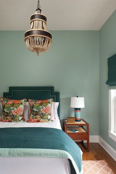 Aqua bedroom adorned w/ a turquoise upholstered bed, nailhead trim and a wood beaded chandelier.