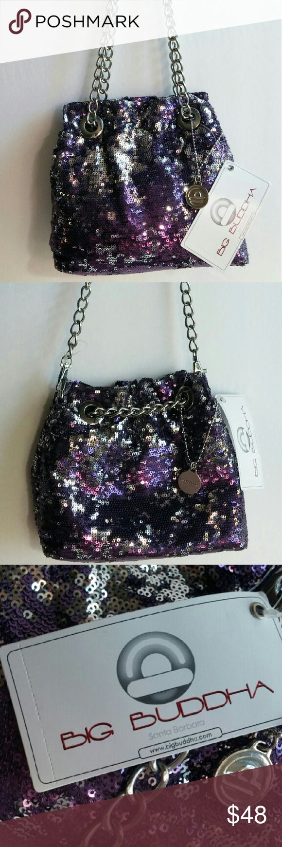 """Big Buddha Purple Sequin Convertible Crossbody Bag This brand new Big Buddha Purple & Sequined Crossbody bag has a detachable chain for a 12 inch strap drop, or pull the fixed chain all the way to one side for a 20 inch strap drop. The inside lining is purple silky fabric. It has a center zip divider pocket, a slip pocket, and the big Buddha logo patch. A logo hanging medallion adorns this little bag. It measures 7"""" Hx 9"""" L x 3.5"""" D. Tag says pink, but the eyes say this bag is indeed purple…"""