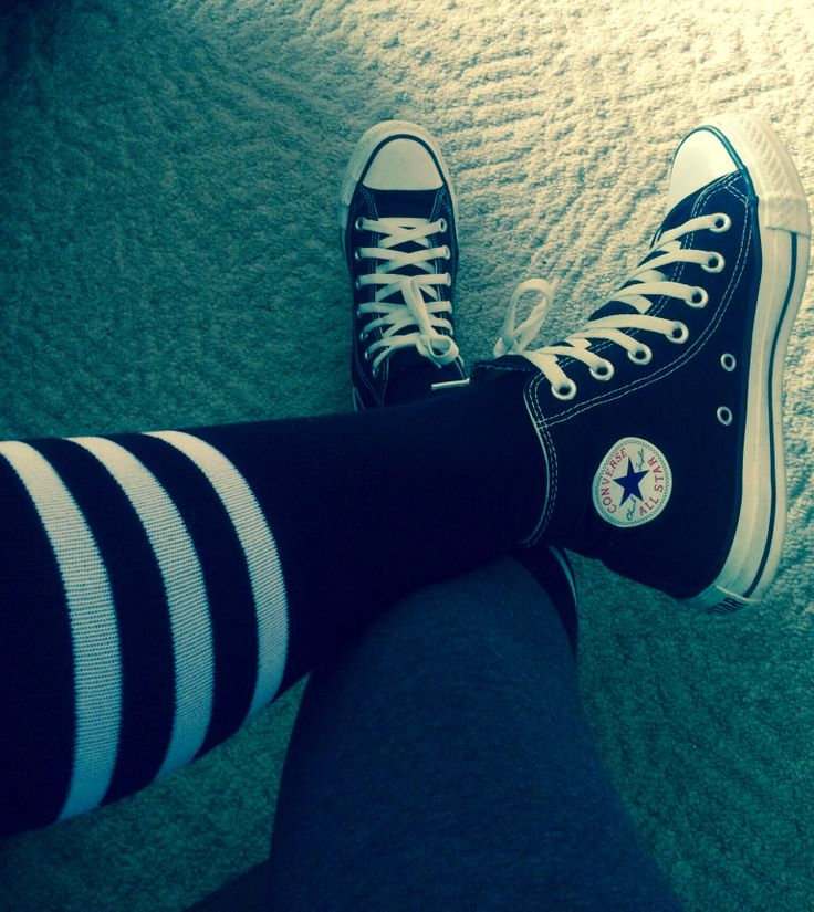 High top converse with knee socks.