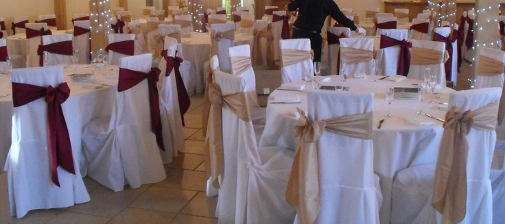 Alternating Gold and Burgundy Satin Side Bows on White Chair Covers
