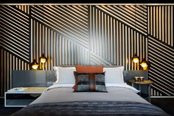 The bedroom gets an angular feature wall behind the bed, which separates it from the dressing room.