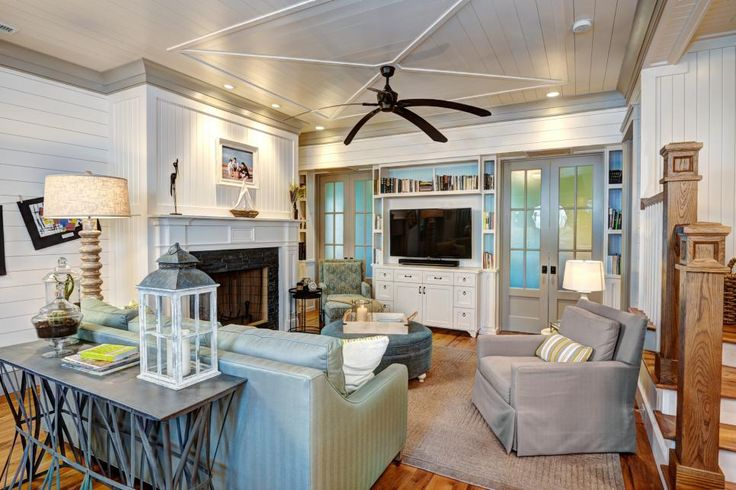One of the benefits of a sharp, white room: There can be many accessories and design items without the space feeling too busy. Here, a coastal-style home boasts a gorgeous fireplace with mantel, TV and loads of comfy furniture. The ceilings and fan add a tropical flair.