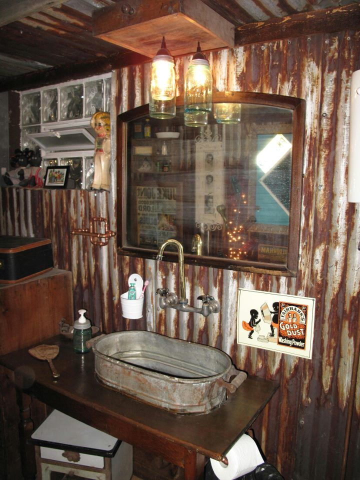 Rusty galvanized walls and sink and ball jar lights. Love it all! This would be so neat in my parents camp house.