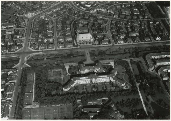 1930, Luchtfoto van de Sportlaan, Segbroeklaan en omgeving. Boven het plantsoen in het midden de R.K. kerk van het Allerheiligste Sacrament, daaronder het Rode Kruisziekenhuis. Rechtsmidden de Oleanderlaan. Linksonder het tennispark aan de Hanenburglaan. 7ed7f619-9184-eef5-bc8a-ea5b1066005d.jpg