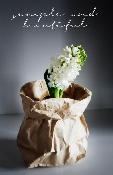 Beautiful Christmas gift a bulb yet to bloom in a simple brown paper bag throw a ribbon on it with a little chalk board painted tag and cursive Merry Christmas this would be practical for wedding favors or hostess gifts