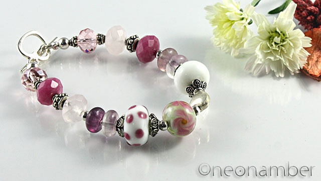 You will Love the hues of pink in this piece! The focal and bigger beads are all lampwork glass beads and glass beads. Accentuated by faceted rose quartz, glass beads and purple and pink colored flourite. Love the brushed heart silver to spice up the look! It complements the sterling silver toggle clasp! Pink lovers, you will adore this piece! $85