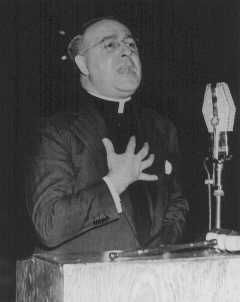 Father Charles Coughlin, leader of the antisemitic Christian Front, delivers a radio broadcast. United States, February 4, 1940.