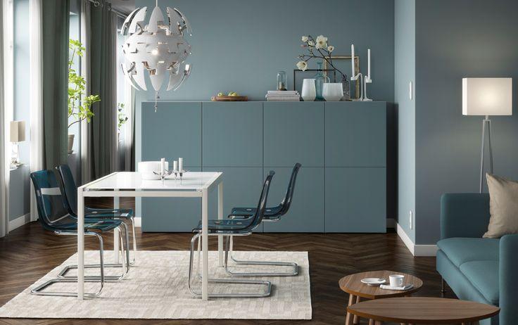 Lichtblauwe eetkamer met glanzend witte tafel en blauwe plastic stoelen.