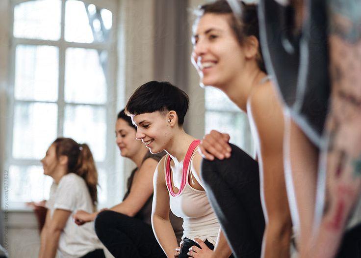 Women in an aerobics class sitting on floor and taking a break