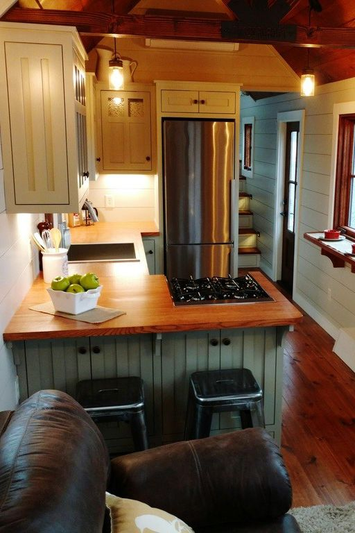 The kitchen features shaker style cabinets with butcher block countertops, stainless steel appliances, and two bar serving areas.