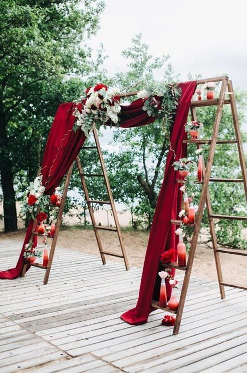 Two ladders lined with small vases are joined by red velvet for a dramatic theatrical effect.