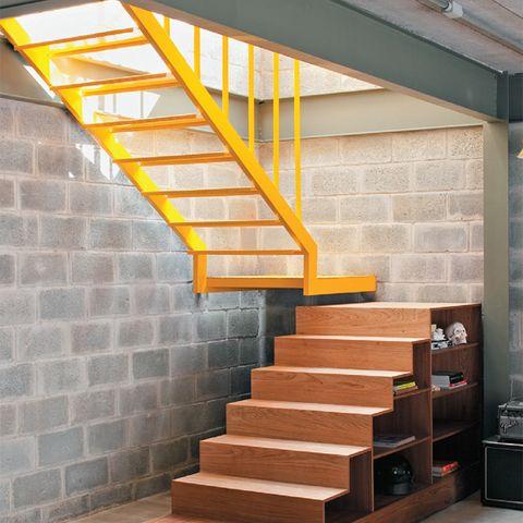 """Acima, a escada desenhada pelo arquiteto foi executada em duas partes. A primeira, fabricada com freijó pela M3 Marcenaria, também funciona como estante dos dois lados. """"Solta, a peça pode ser encostada na parede e mudar a forma de circulação."""" A parte de aço (Jet Calhas) recebeu esmalte sintético brilhante Coralit (Coral)."""