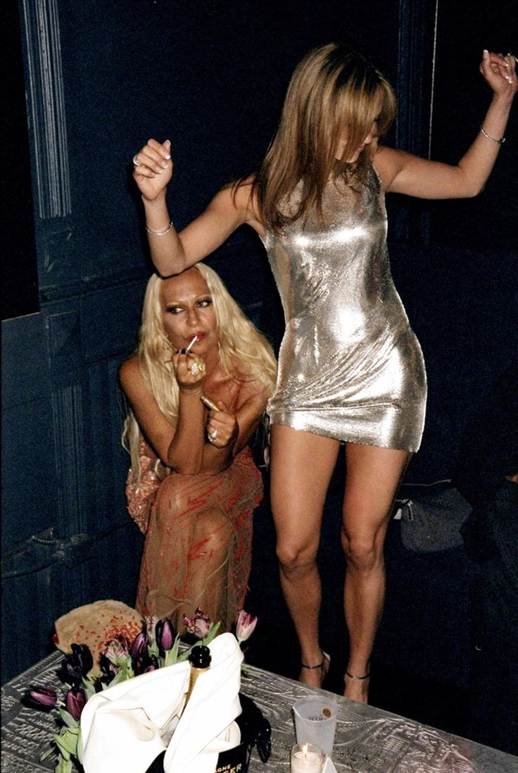 """Jennifer Lopez dances on a table while Donatella Versace reapplies lip gloss at a """"Notorious"""" magazine party hosted at the Limelight nightclub in 1999."""