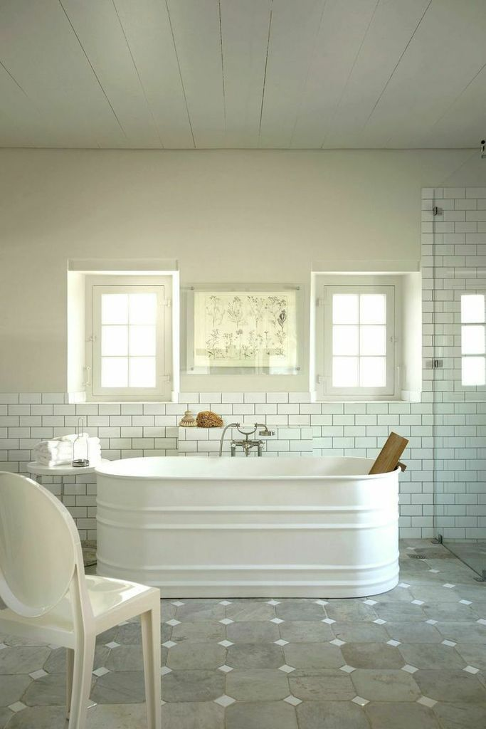 Bathroom with freestanding soaking tub with wood backrest that hangs on the side. This is produced, but possible DIY by having a galvanized stock trough powder coated and plumbed. Interesting.