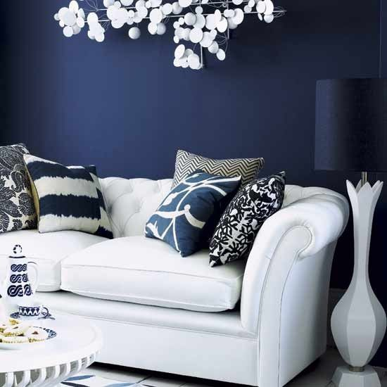A midnight blue backdrop allows white furniture and accessories to stand out dramatically, creating a stunning setting. Cool, contemporary patterns add a modern touch to the classic sofa. The wall is painted in Drawing Room Blue