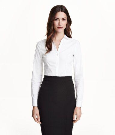 Camisa elástica de corte ajustado. Mangas largas. Escote de pico y botones en la parte delantera y en los puños.