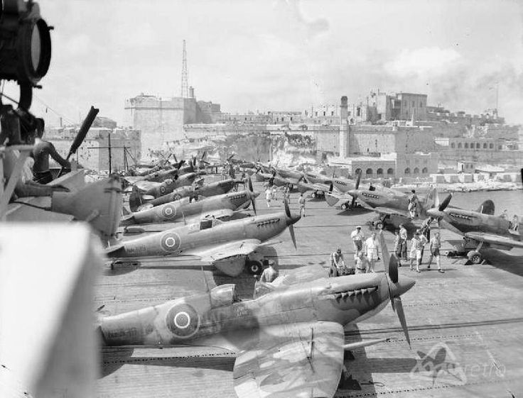Malta at war: A packed aircraft carrier arrives under the bombed bastions of the entrance to Valletta's Grand Harbour during the war