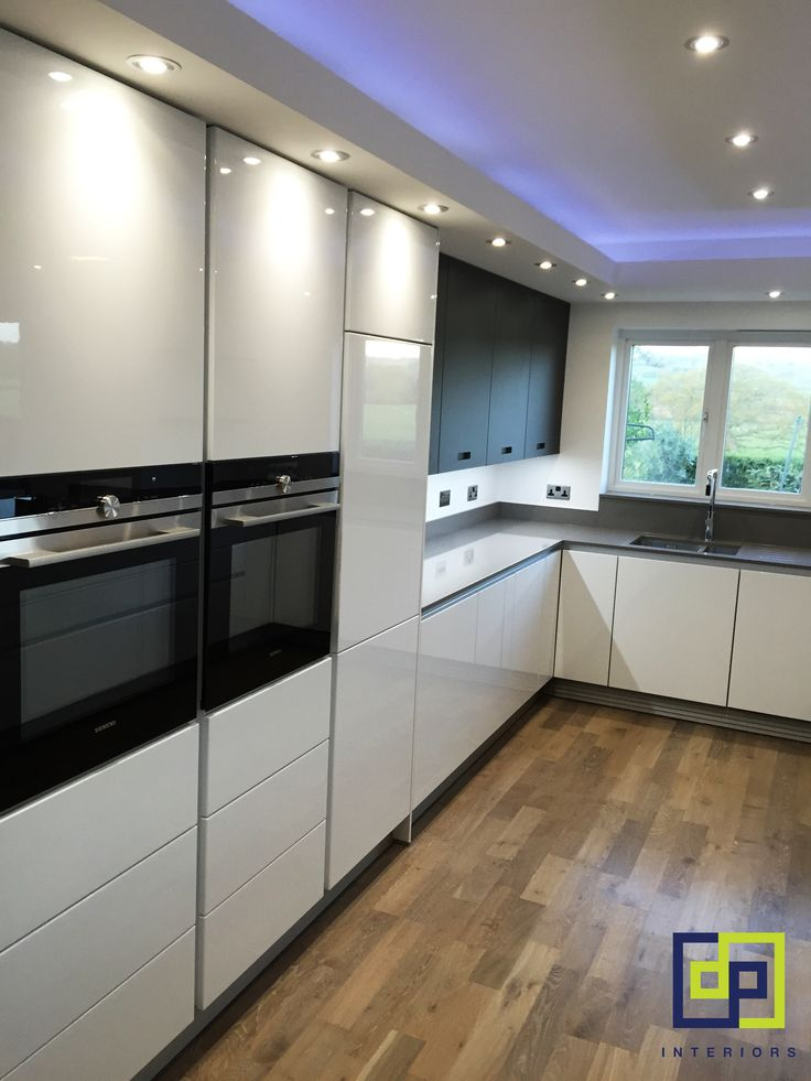 kitchen halo lighting feature. white gloss and black glass wall units. German kitchen