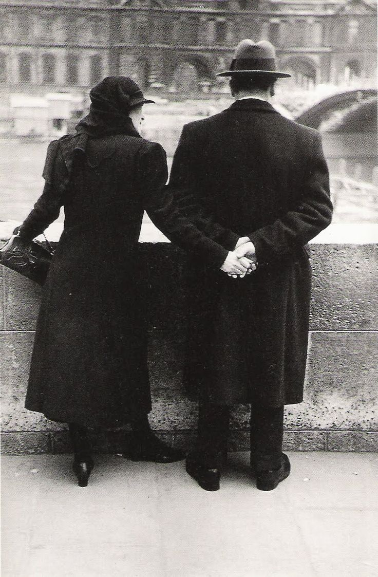 John Phillips --  French couple holding hands as they look out on River Seine. Paris, 1937