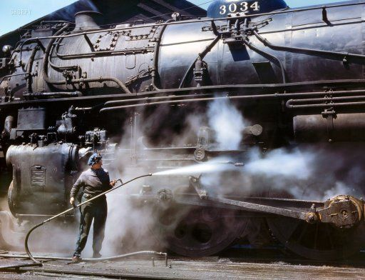 """April 1943. """"Viola Sievers, one of the wipers at the Chicago & North Western roundhouse, giving a giant """"H"""" class locomotive a bath of live steam at Clinton, Iowa. Mrs. Sievers is the sole support of her mother and has a son-in-law in the Army."""" Kodachrome transparency by Jack Delano."""
