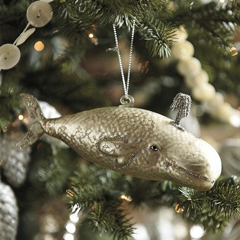Part of our Nordic Seaside Holiday collection, this fetching fellow is destined to become a favorite at your next tree-trimming party. Made of golden hand blown glass and decorated with glittering gold spout. His fins, tail and mouth are lined in glitter for extra sparkle.