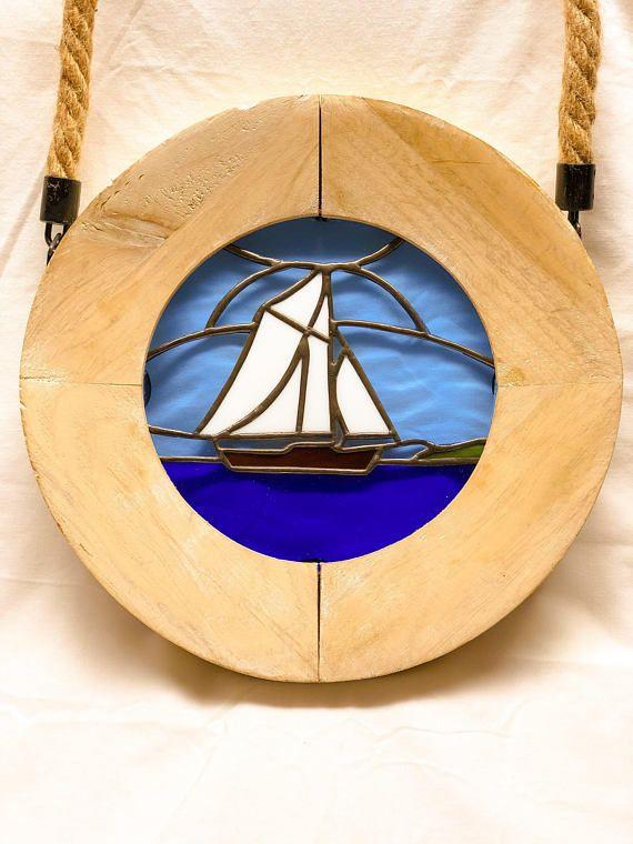Dit is een mooie houten Patrijspoort met gebrandschilderd glas zeilboot in de zee suncatcher! Toevoegen aan uw maritieme collectie met deze prachtige handgemaakte stuk weergegeven in uw favoriete venster! Het buitenste deel van de patrijspoort is gemaakt van hout met een touw