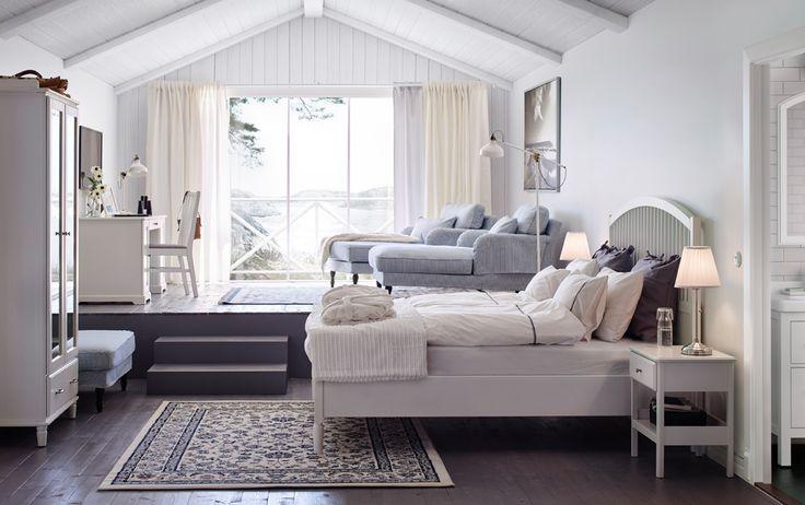 Ein großes Hotelzimmer u. a. eingerichtet mit TYSSEDAL Bettgestell in Weiß, weißen Ablagetischen und einem Kleiderschrank mit Spiegeltüren