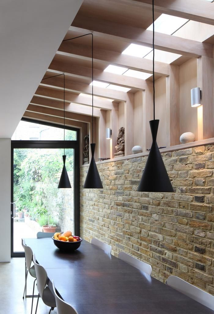 Tom Dixon beat lights tall in black with brick party wall and Oak addition in London townhouse