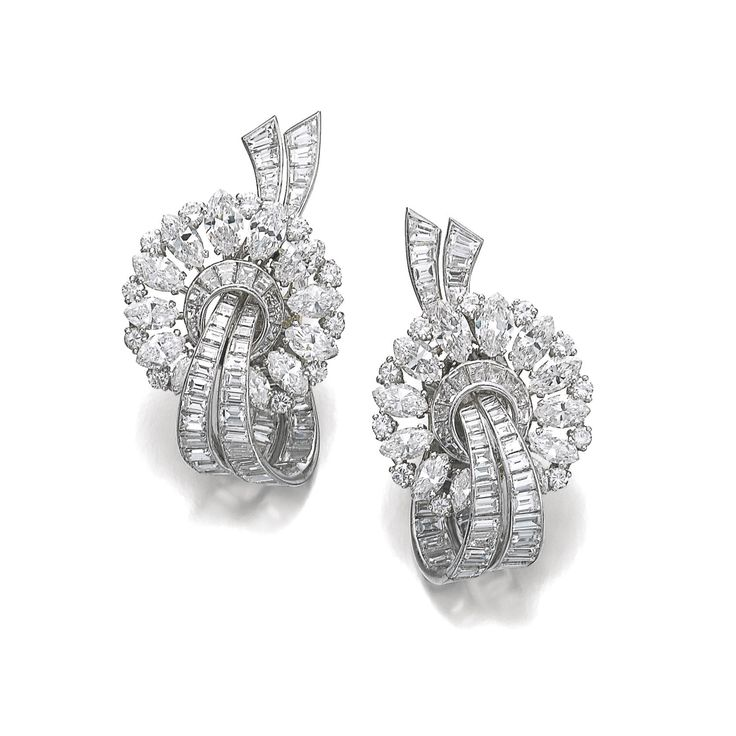 Pair of diamond dress clips, Van Cleef & Arpels, 1950s. Each set with marquise-shaped and circular-cut diamonds forming a circle around a ribbon motif composed of baguette diamonds, clip and collapsible post fitting, each signed Van Cleef & Arpels, numbered, French assay marks, one with French maker's mark.