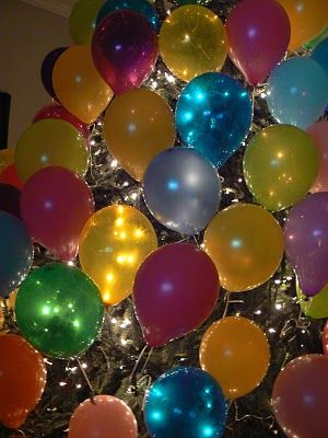 On New Year's Eve, Remove the Christmas ornaments from your tree and replace them with small balloons filled with New Years' wishes. Tie the balloons to the tree with ribbon, being careful not to pop them. You can finish decorating the tree by filling it with New Years confetti and New Year's hats. As the New Year rings in, guests can pop the balloons and claim the wishes/money inside the balloon! I am totally doing this!!