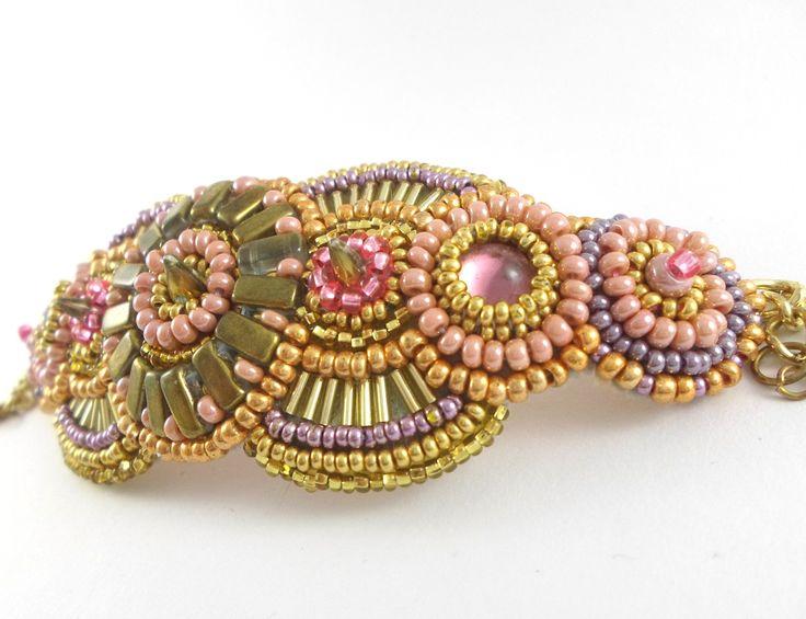 Růžové zlato, náramek Náramek Růžové zlato je zhotoven ze tří ostnů ve středové části a dvou skleněných růžových kabošonů po stranách obšitých růžovým a zlatým Preciosa rokajlemazlatými našívacími obdélníčky. Hlavními barvami jsou odstíny zlaté a růžové, doplněné kovově fialovou. Náramek je zhotoven metodoukorálkové výšivky a pejotového ...
