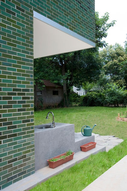 The green comes from variegated glazed bricks, but up close I'm drawn to the the built-in sink in the concrete counter/bench aligned with the side wall. It looks like the owners thought of everything they wanted with the outdoor space.