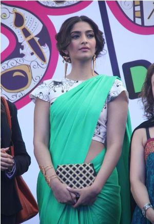 @Sonam Kapoor in a green @MasabaG http://www.houseofmasaba.com/ Saree with fun cow print blouse & interesting purse
