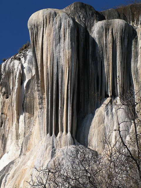 """Hierve El Agua """"the water boils"""", Oaxaca, Mexico ~The site consists of two rock shelves or cliffs which rise between fifty and ninety meters from the valley below, from which extend nearly white rock formations which look like waterfalls. These formations are created by fresh water springs, whose water is over saturated with calcium carbonate and other minerals. As the water runs over the cliffs, the excess minerals are deposited, much in the same manner that stalactites are formed in caves."""