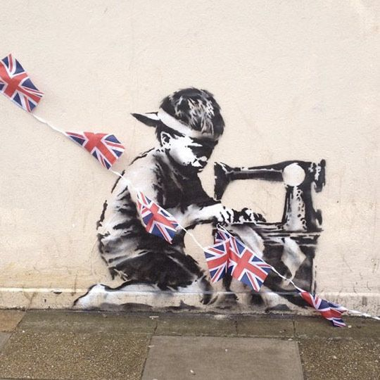 A new Banksy piece has appeared on the side of Poundland, Whymark Avenue, London. The stencil depicts a child hard at work sewing some Union Jack bunting, of course another statement on child labour.