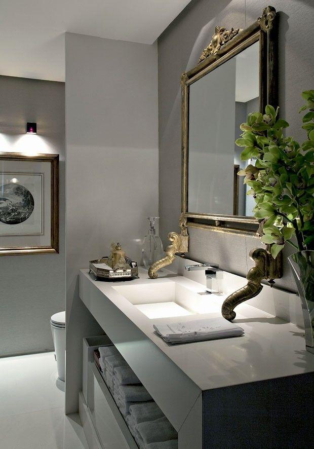 Concebido pelo designer de interiores Marco Aurélio Viterbo, o ambiente de 4,50 m² tem paredes revestidas com seda da Safira Sedas, na cor cinza com nuances em prata. A tonalidade faz contraponto ao off-white da pedra Caesarstone, da Marmobello, usada na bancada da pia e no piso. O dourado das molduras do espelho e da gravura, ambos da Orbi Brasil, é destacado pela iluminação embutida na sanca e da luminária Cubetto, na Wall Lamps. Sobre a bancada, bandeja e perfumeiro da Baccarat.