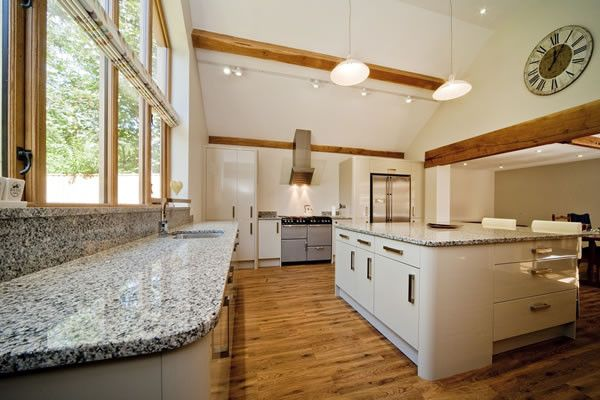 luna pearl granite with modern white kitchen cabinets and earthy hardwood flooring